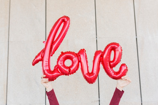 愛の形の単語で赤い風船を保持している女性の手。アウトドアライフスタイル
