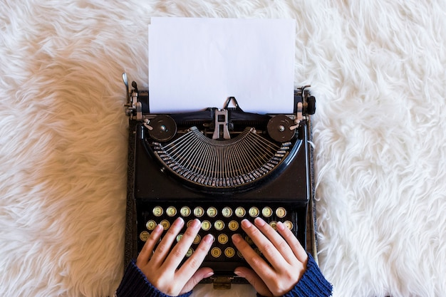 レトロタイプライターで入力する女性の手のクローズアップ。コーヒーのカップは右側にあります。上面図。
