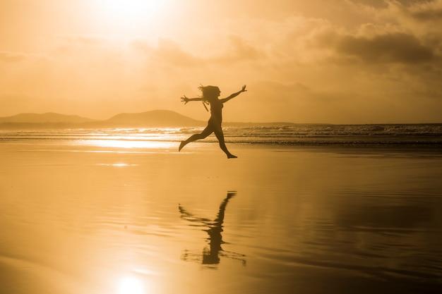 海岸でビーチでジャンプ若い美しい女性のシルエット。日没。黄色い空。ランサローテ島、カナリア諸島