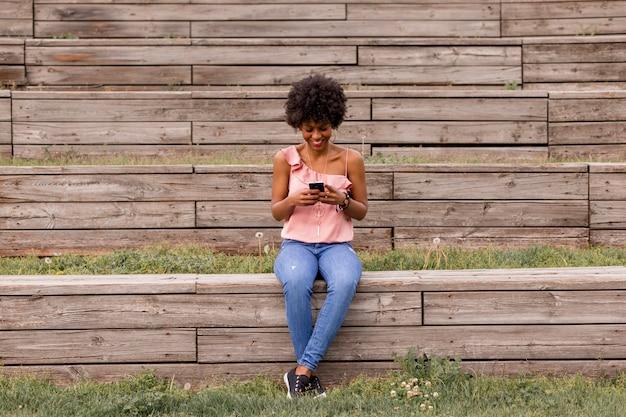 携帯電話を使用して、木製の階段に座って、笑顔の美しい若いアフロアメリカンの女性。ウッドの背景。アウトドアライフスタイル
