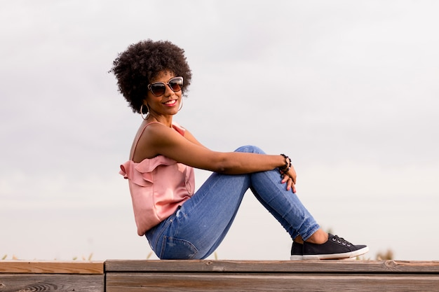 木製の階段の上に座って、笑顔幸せな若い美しいアフロアメリカンの女性の肖像画。曇りの背景。春または夏のシーズン。カジュアルな服。