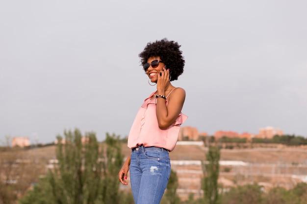幸せな若い美しいアフロアメリカンの女性は笑みを浮かべて、彼女の携帯電話で話しています。都市の背景。春または夏のシーズン。カジュアルな服