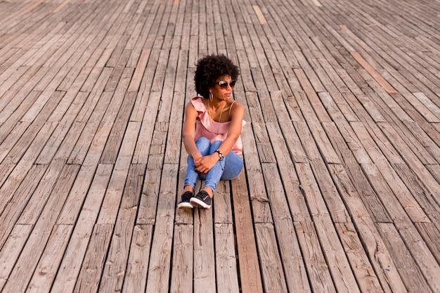Портрет счастливой молодой красивой афро-американской женщины, сидя на деревянный пол и улыбается. весна или лето. повседневная одежда