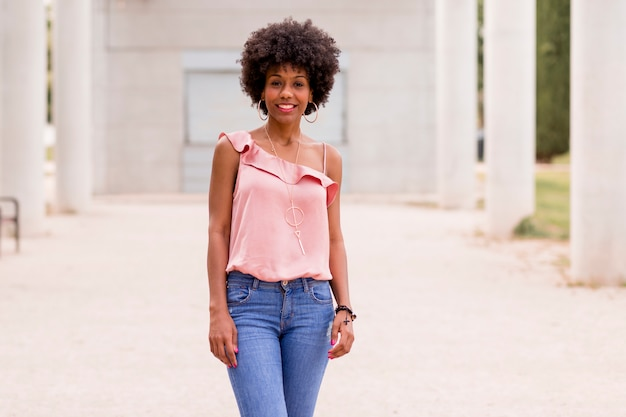 笑って幸せな若い美しいアフロアメリカンの女性。白い列の背景。春または夏のシーズン。カジュアルウェアアウトドア