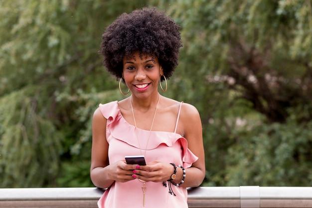 幸せな若い美しいアフロアメリカンの女性は笑みを浮かべて、携帯電話を使用しています。緑の背景。春または夏のシーズン。カジュアルウェアアウトドア