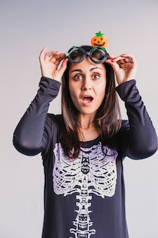 面白いハロウィーンのメガネを着て、笑顔の若い女性。屋内でのライフスタイル。スケルトン衣装