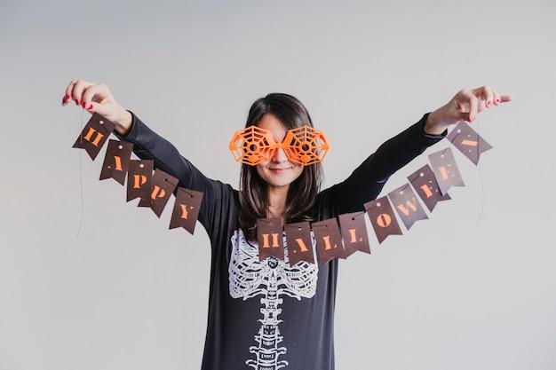 Молодая женщина держа гирлянду с счастливым знаком хеллоуина. стиль жизни в помещении. костюм скелета