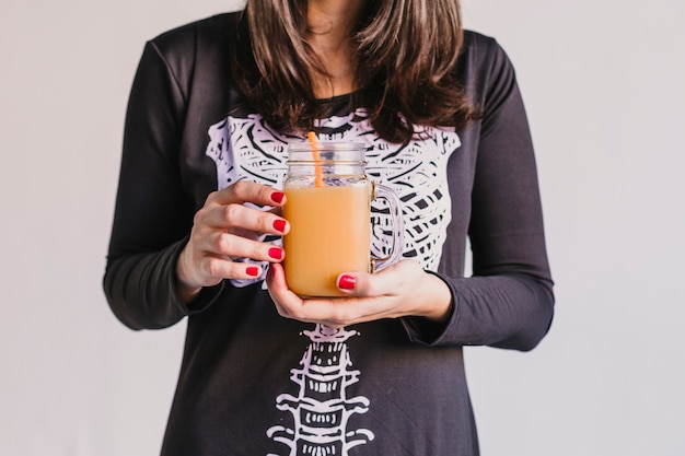 Крупным планом вид молодой красивой женщины, держащей апельсиновый сок. одет в черно-белый костюм скелета. хэллоуин концепция