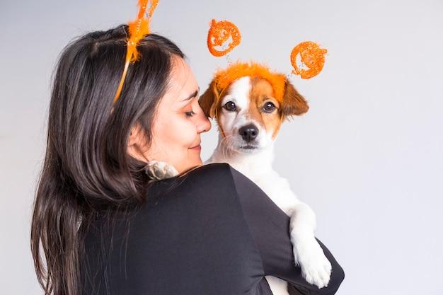 白い背景の上の彼女のかわいい小型犬を保持している若い女性。一致するカボチャディアデム。ハロウィーンのコンセプト
