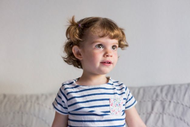 Красивая маленькая девочка, стоя на кровати и улыбается. весело, дома, в помещении. стиль жизни
