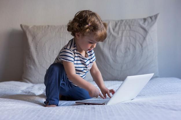 Красивая маленькая девочка используя компьтер-книжку на ее кровати родителей. дома, в помещении. стиль жизни
