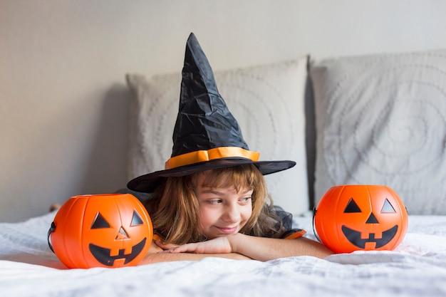 ベッドに笑みを浮かべて、ハロウィーンの衣装を着て美しい少女。カボチャと遊ぶ