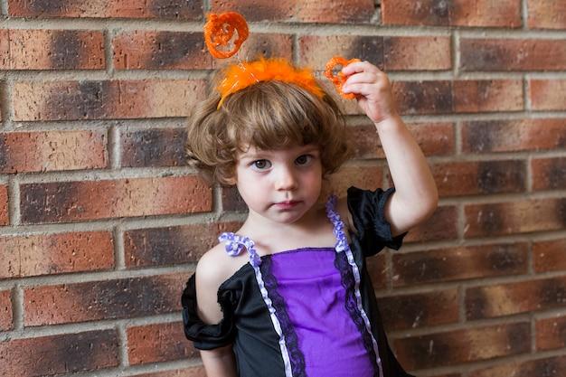 Красивая маленькая девочка улыбается и носить костюм хэллоуина