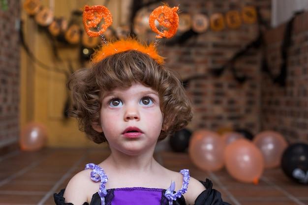 Красивая маленькая девочка в костюме хэллоуина. играть с тыквами