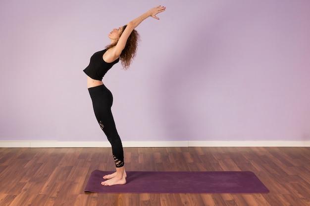 Йога красивой молодой женщины практикуя внутри помещения
