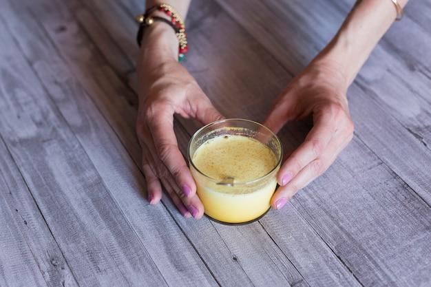 黄色のジュースとガラスを保持している女性の手の平面図です。灰色の木のタブレット。昼間。健康とライフスタイルのコンセプト