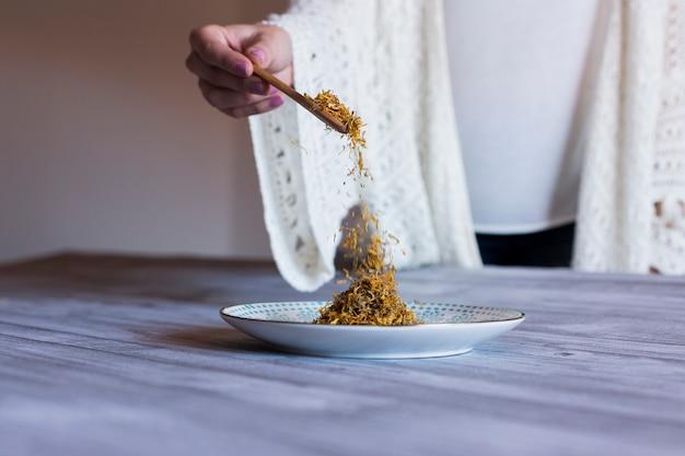 Взгляд сверху рук женщины держа ложку с желтой куркумой. серый деревянный стол фон. дневная концепция здорового образа жизни