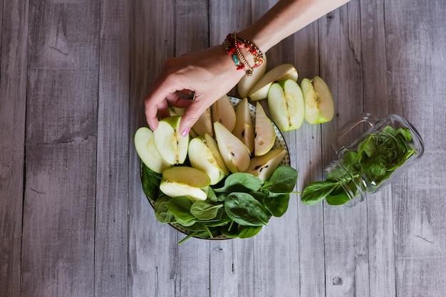 Еда здорового завтрак со свежими фруктами и овощами, как яблоко, груша и шпинат. рука женщины, поместив кусок зеленого яблока. чистая еда, диета, детокс, концепция вегетарианской пищи