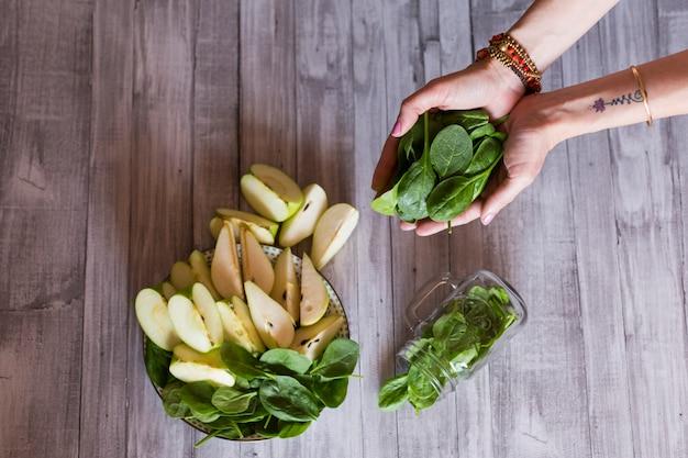 Еда здорового завтрак со свежими фруктами и овощами, как яблоко, груша и шпинат. женщина рука кучу шпината. чистая еда, диета, детокс, концепция вегетарианской пищи