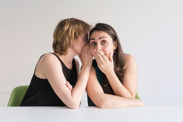 Две красивые женщины на белом фоне. блондинка рассказывает секрет на ухо своей брюнетке, и она выглядит удивленной. концепция дружбы и секретов