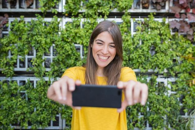 携帯電話で写真を撮る美しい若い女性の屋外の肖像画。黄色のカジュアルなシャツを着て、笑顔。ライフスタイルと楽しみ。緑の背景