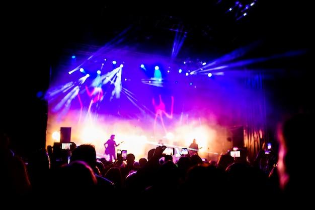 夜のパフォーマンスを楽しんでいる多くの人々の写真、コンサートで挙手と携帯電話で踊る大規模な認識できない群衆。ナイトライフ