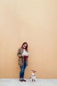 若い女性と地図を探している都市のかわいいジャックラッセル犬。旅行の概念