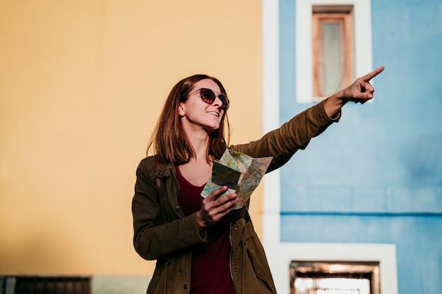 黄色と緑の壁の上の地図を読む若い女性。旅行の概念