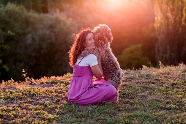 Молодая женщина владельца с ее коричневой испанской водяной собакой, весело проводящей время на открытом воздухе в парке на закате. концепция любви к животным