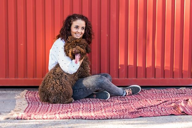 Красивая молодая женщина обнимая ее собаку, коричневую испанскую собаку воды. она улыбается и любит собаку. любовь к животным