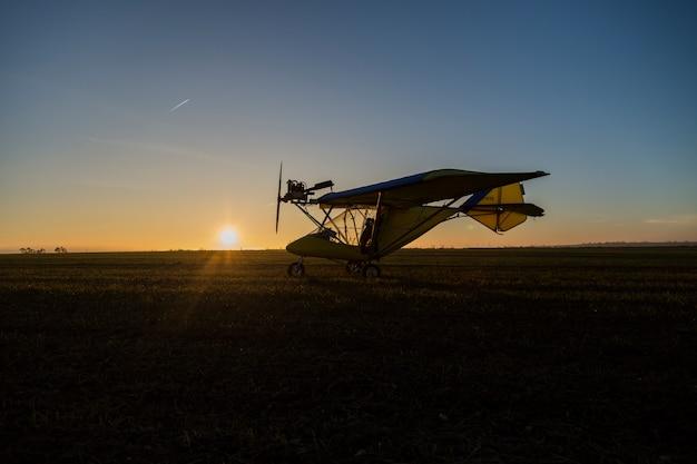 日没時の地面に軽飛行機のシルエット。旅行の概念