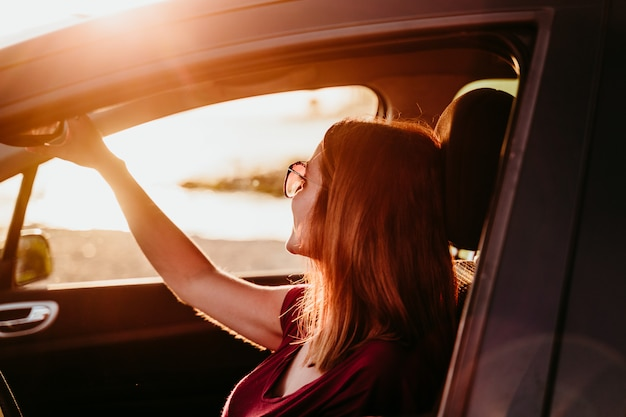 Молодая женщина за рулем автомобиля на закате. концепция путешествия