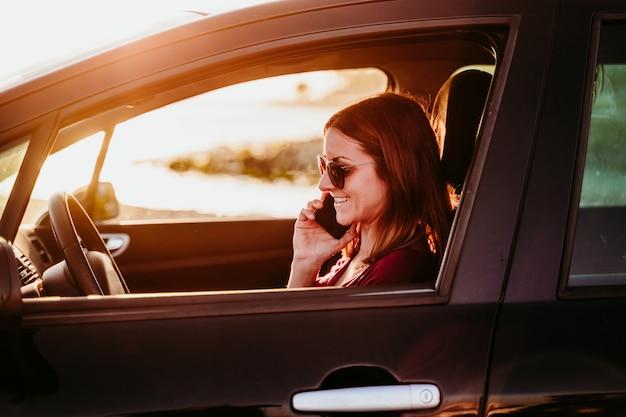 日没で車を運転し、携帯電話を使用して若い女性。旅行の概念