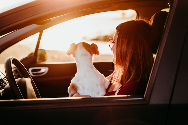 若い女性と夕暮れ時の車の中で彼女のかわいいジャックラッセル犬。旅行の概念