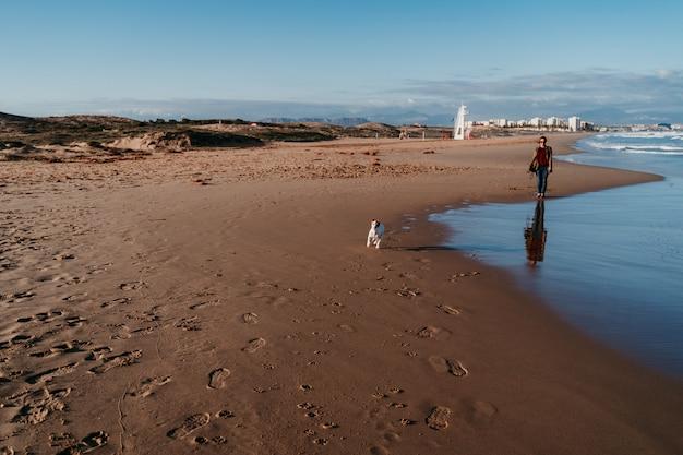 Молодая женщина и ее собака на пляже на закате