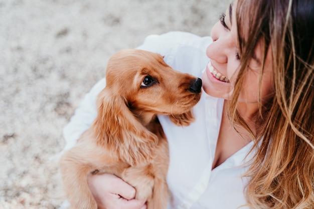 Молодая женщина и ее милый щенок кокер-спаниеля на открытом воздухе в парке
