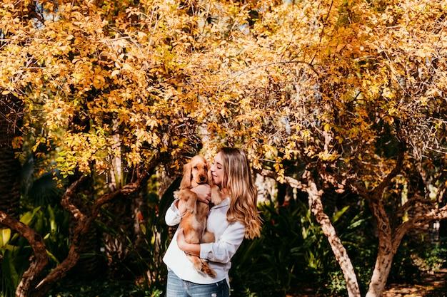 Молодая женщина и ее милый щенок кокер-спаниель собака на открытом воздухе в парке. солнечная погода.