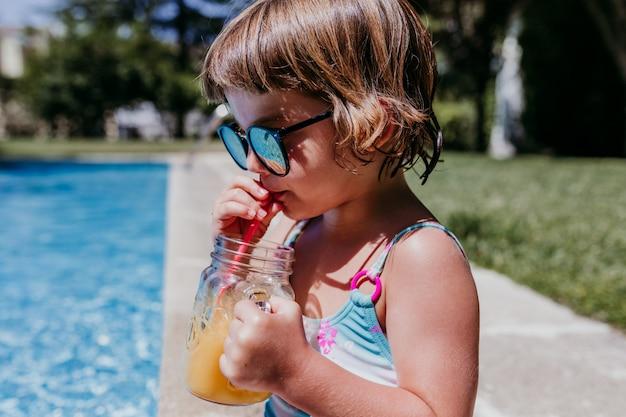 Красивая девочка ребенка в бассейне, пьющем здоровый апельсиновый сок и весело проводящем время на открытом воздухе. летнее время и концепция образа жизни