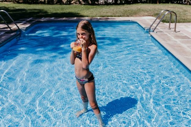 Красивая девочка подростка в бассейне, пьющем здоровый апельсиновый сок и весело проводящем время на открытом воздухе. летнее время и концепция образа жизни