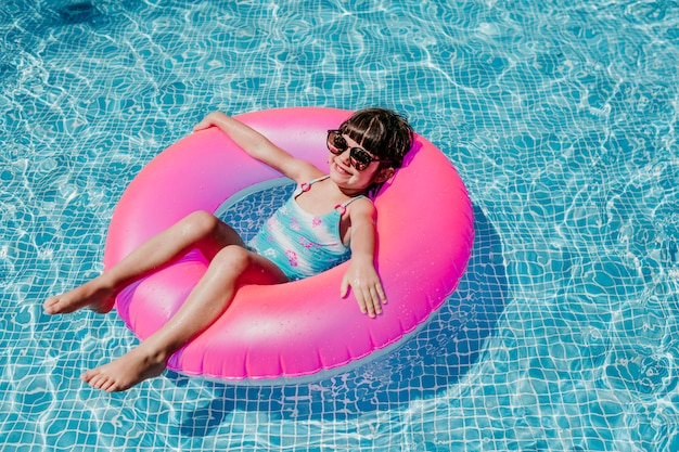 プールでピンクのドーナツに浮かぶ美しい子供の女の子。サングラスをかけ、笑顔。楽しさと夏のライフスタイル