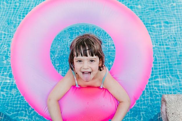 プールでピンクのドーナツに浮かぶ美しい子供の女の子。笑顔。楽しさと夏のライフスタイル