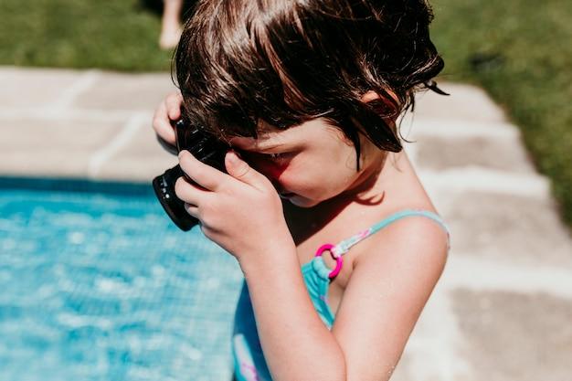 プールで古いビンテージカメラで写真を撮る美しい子供の女の子。笑顔。楽しさと夏のライフスタイル