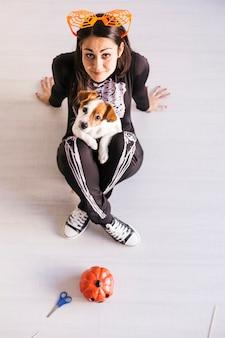 ハロウィンの準備をしているかわいい小さな犬を着た若い女性の平面図です。スケルトンの衣装を着ている女性。ハロウィーンのコンセプト。屋内で