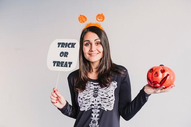 Молодая женщина держа тыкву и знак фокуса или обслуживания. одет в черно-белый костюм скелета. концепция хэллоуин в закрытом помещении. стиль жизни