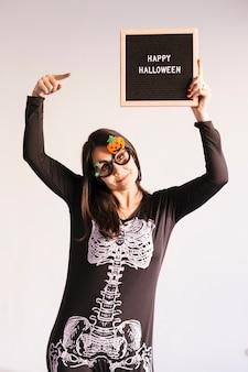 幸せなハロウィーンのサインと黒のビンテージレターボードを保持している若い女性。屋内でのライフスタイル。スケルトン衣装