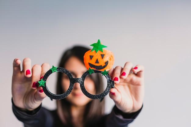 Молодая женщина в смешных очках хэллоуин и улыбается. стиль жизни в помещении. костюм скелета