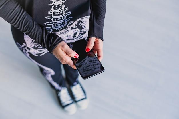 Взгляд сверху молодой женщины используя мобильный телефон. одет в черно-белый костюм скелета. концепция хэллоуин в закрытом помещении. технологии