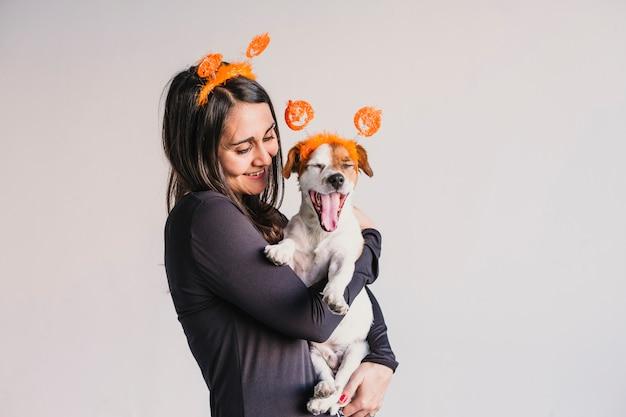 Молодая женщина, держащая ее милая маленькая собака над соответствующие тыквенные диадемы. концепция хэллоуин в помещении