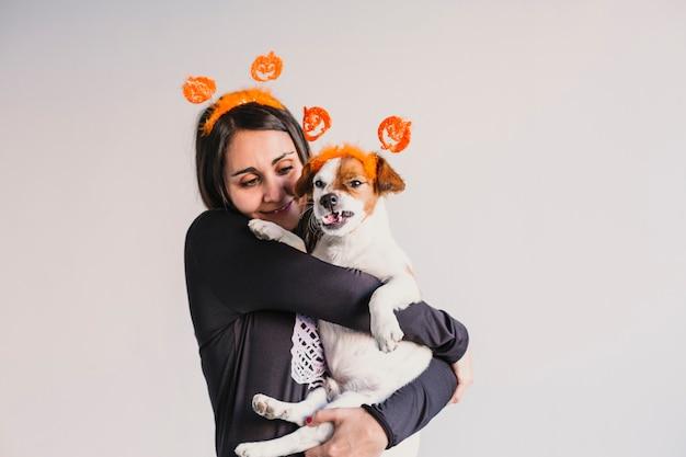 一致するカボチャディアデムに彼女のかわいい小型犬を保持している若い女性。ハロウィーンのコンセプト。屋内で