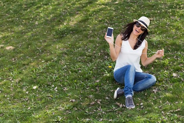 Красивая молодая женщина, слушать музыку на своем смартфоне. она танцует и веселится на природе.